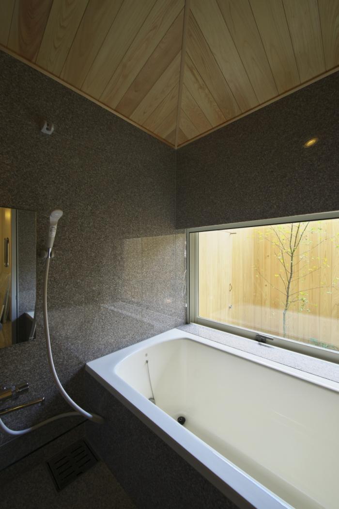 浴室から塀に囲まれた坪庭を見る