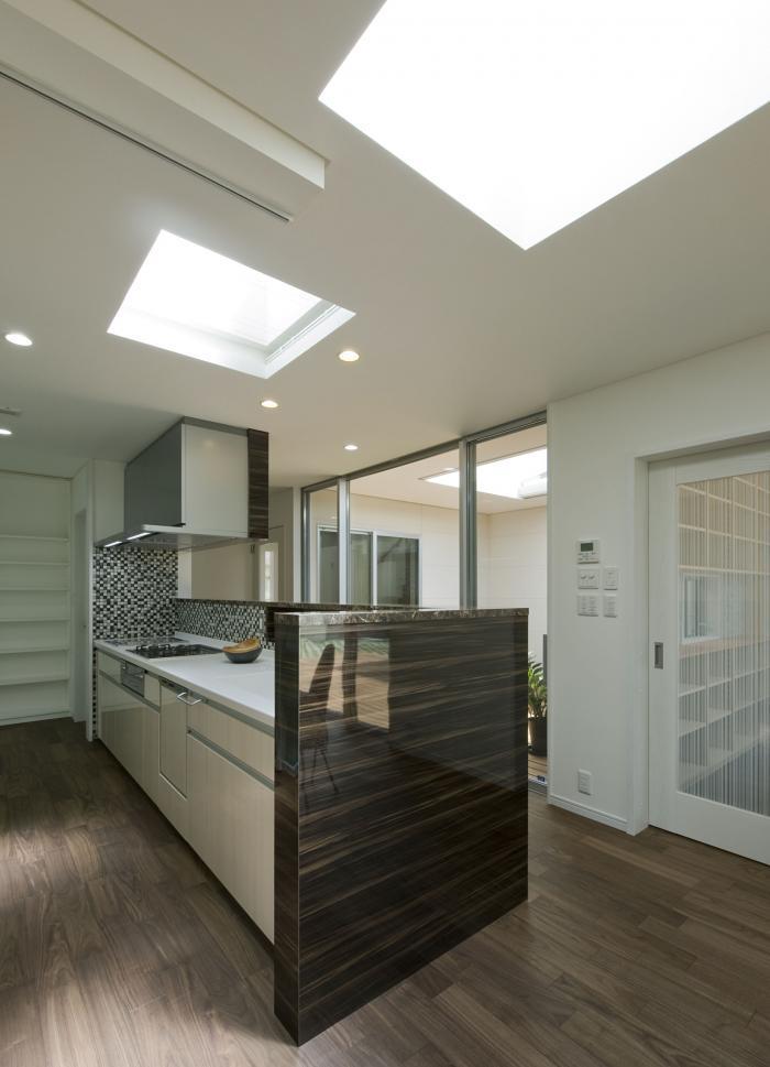 3つのデッキテラスを囲むコートハウス・キッチンと側面に扉なし(ロールブラインド付き)の食品庫
